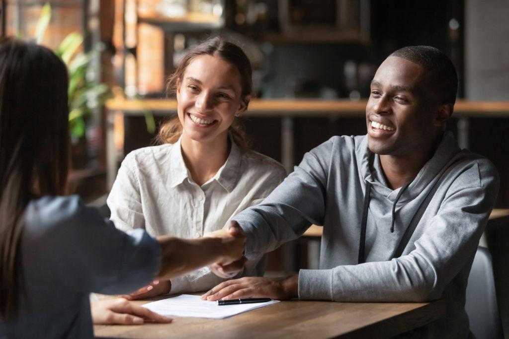 homem cumprimentando um cliente satisfeito com uma mulher sorridente ao seu lado